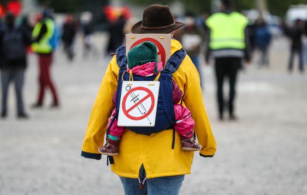 Une manifestante porte un panneau signalant son opposition à un vaccin contre le coronavirus,...