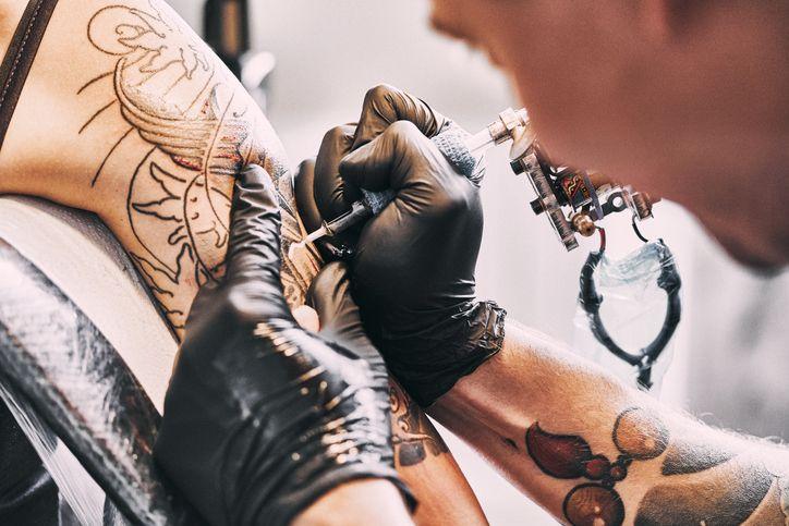 Artiste de tatouage faisant un tatouage sur une épaule (image