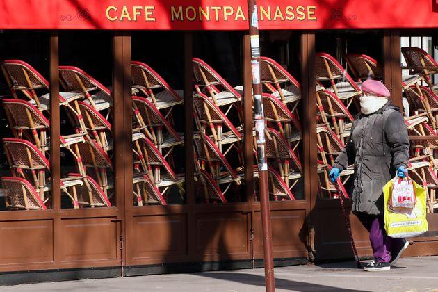 Une femme marche en face d'un restaurant fermé le 24 mars 2020, à