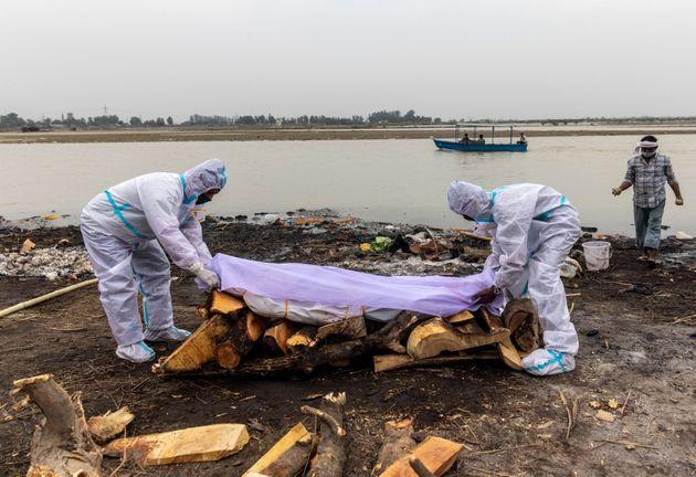 Des hommes placent un tissu blanc sur le corps d'un proche décédé du COVID-19 avant...