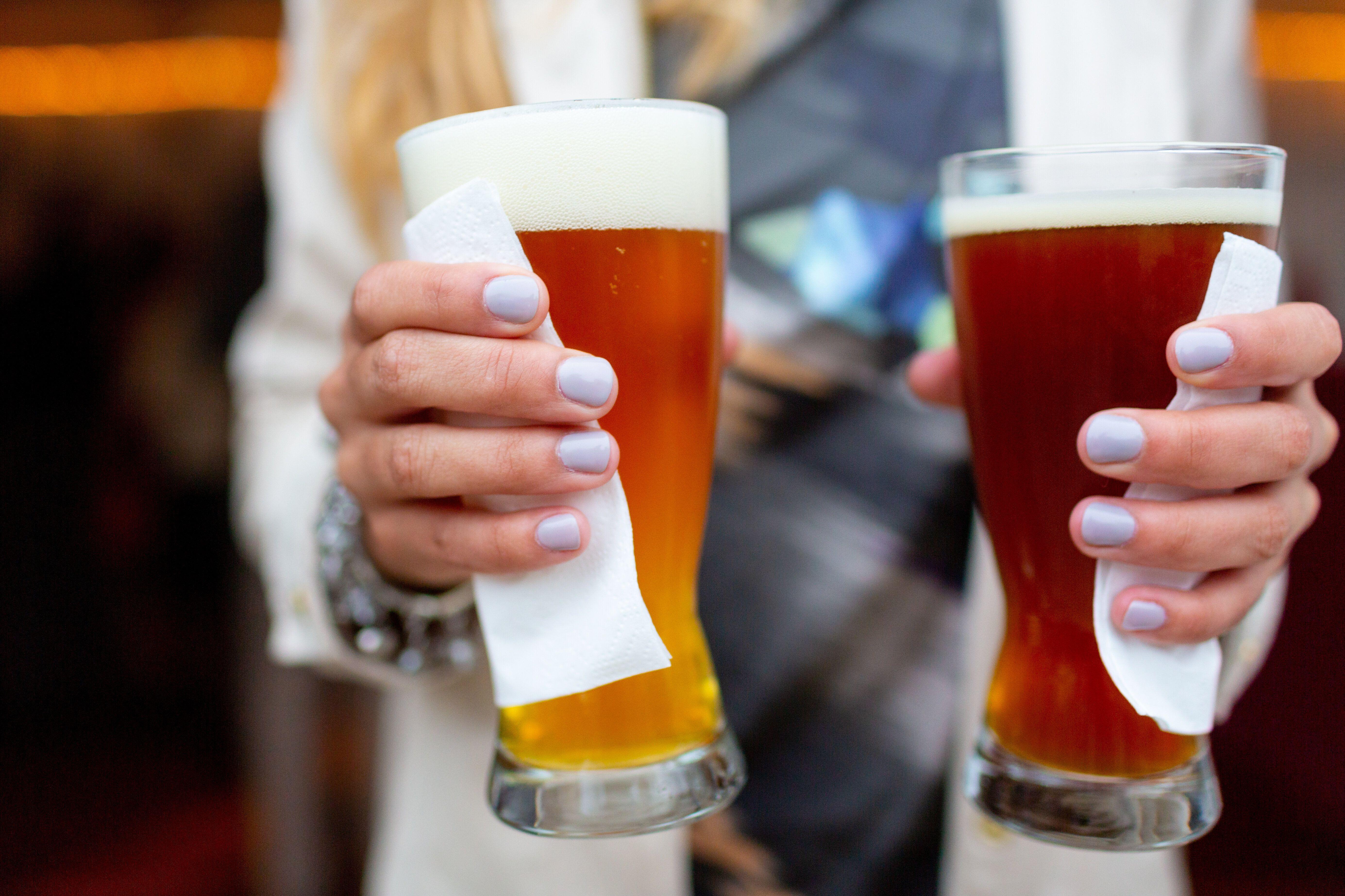 Une femme tenant deux verres de bières dans ses