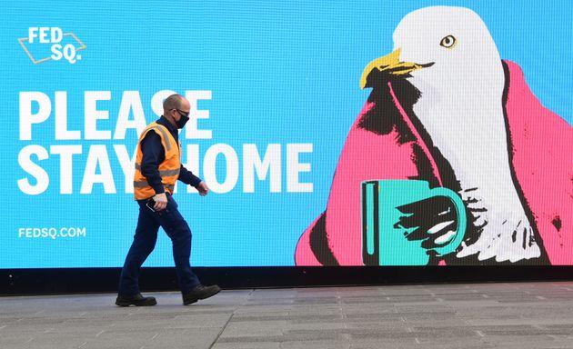 Un passant devant un panneau encourageant la population à rester chez soi à Melbourne le...