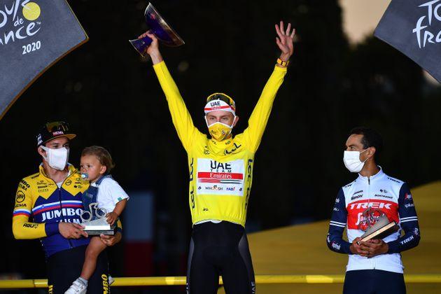 Tadej Pogacar, maillot jaune de la précédente édition, accompagné sur le...