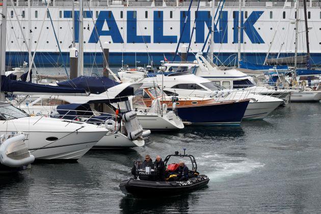 (Photo: des membres des forces de l'ordre patrouillent en bateau autour du bâtiment qui accueille les...