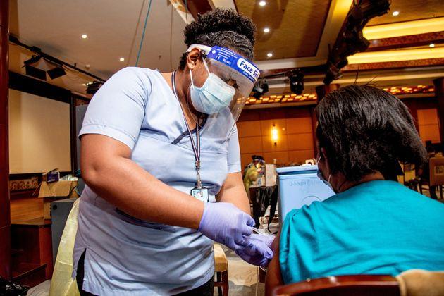 Une soignante injecte une dose de vaccin AstraZeneca à une habitante de Suva, aux îles