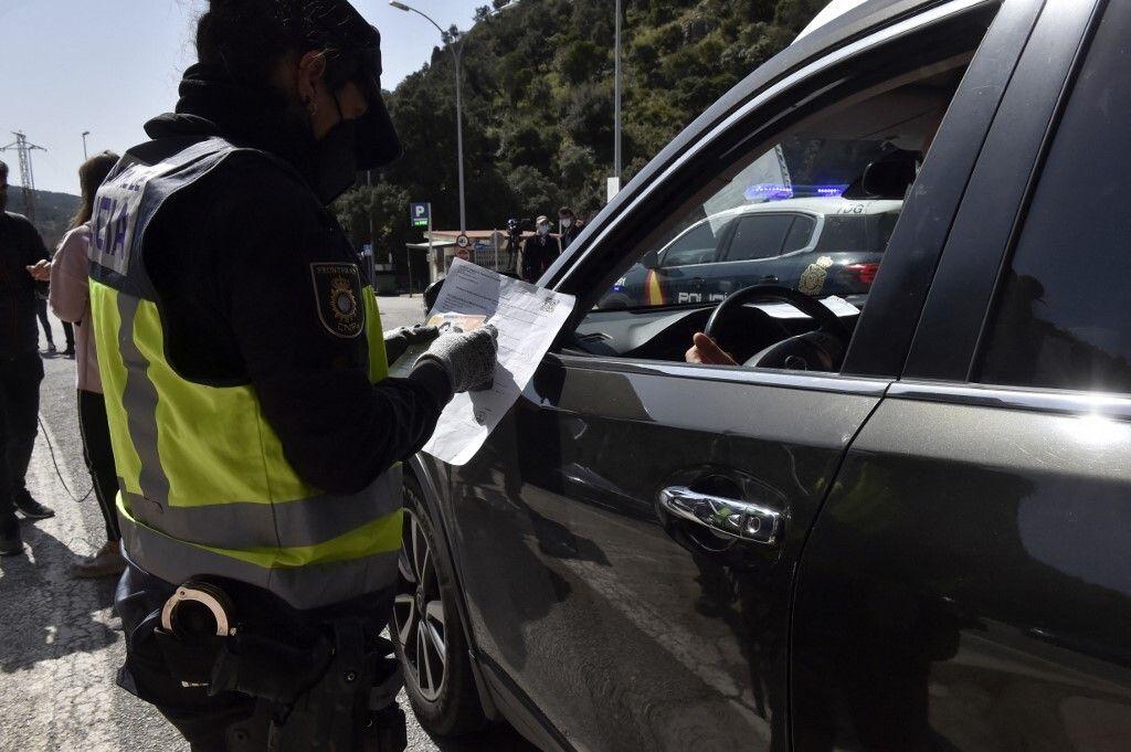 Un policier espagnol vérifie le test d'un automobiliste à la frontière avec la France,...