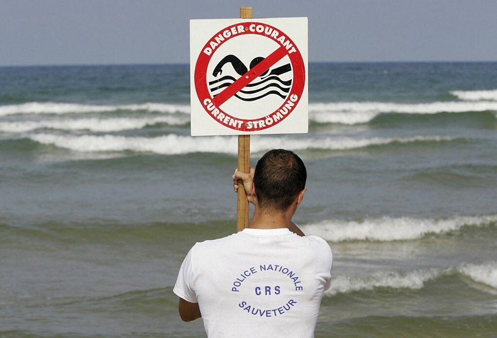 Un CRS maître-nageur-sauveteur installe un panneau indiquant la présence de courants de baïne, le 21...