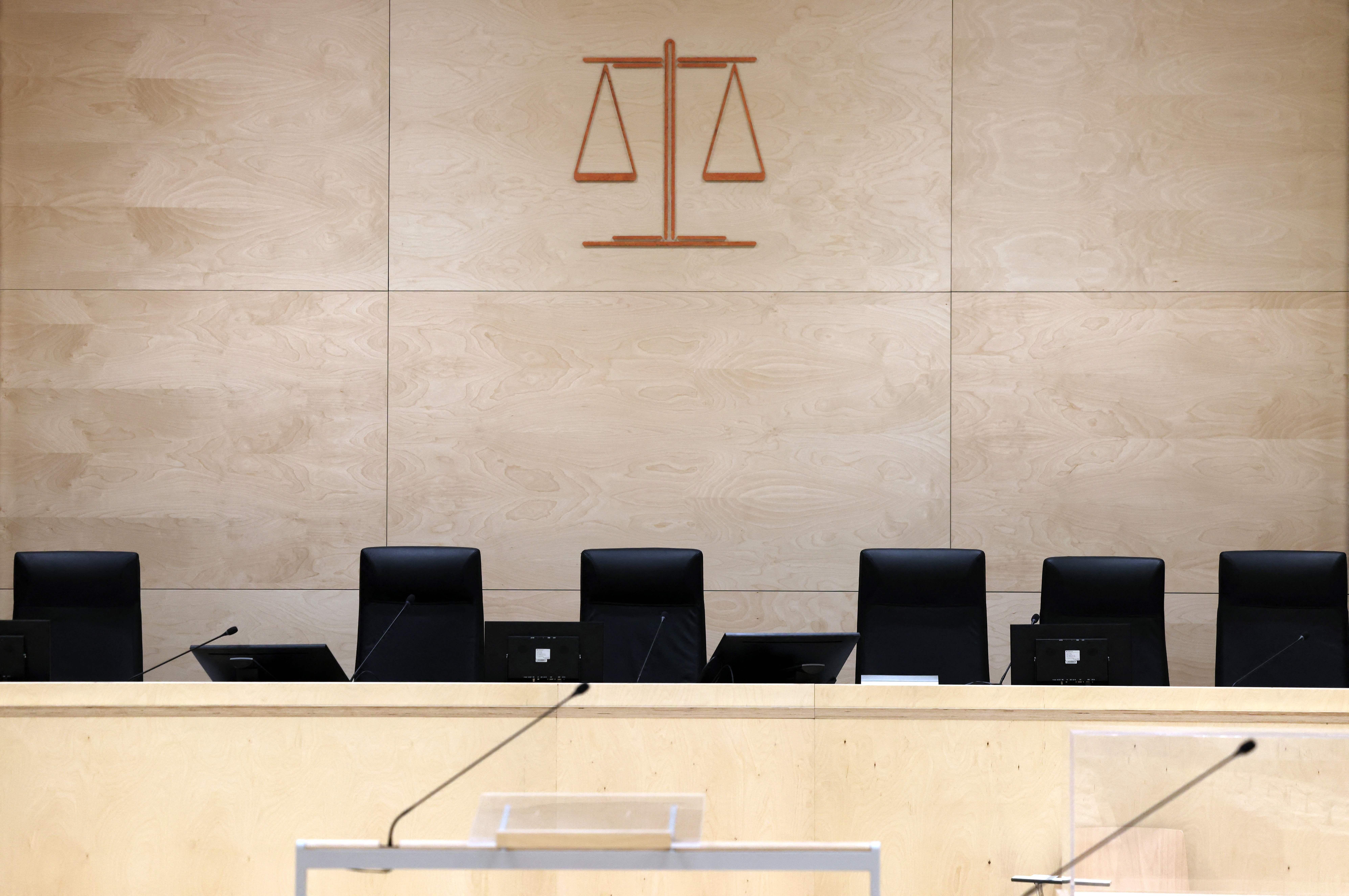 Le symbole de la Justice au-dessus des sièges des juges dans la salle d'audience temporaire installée...