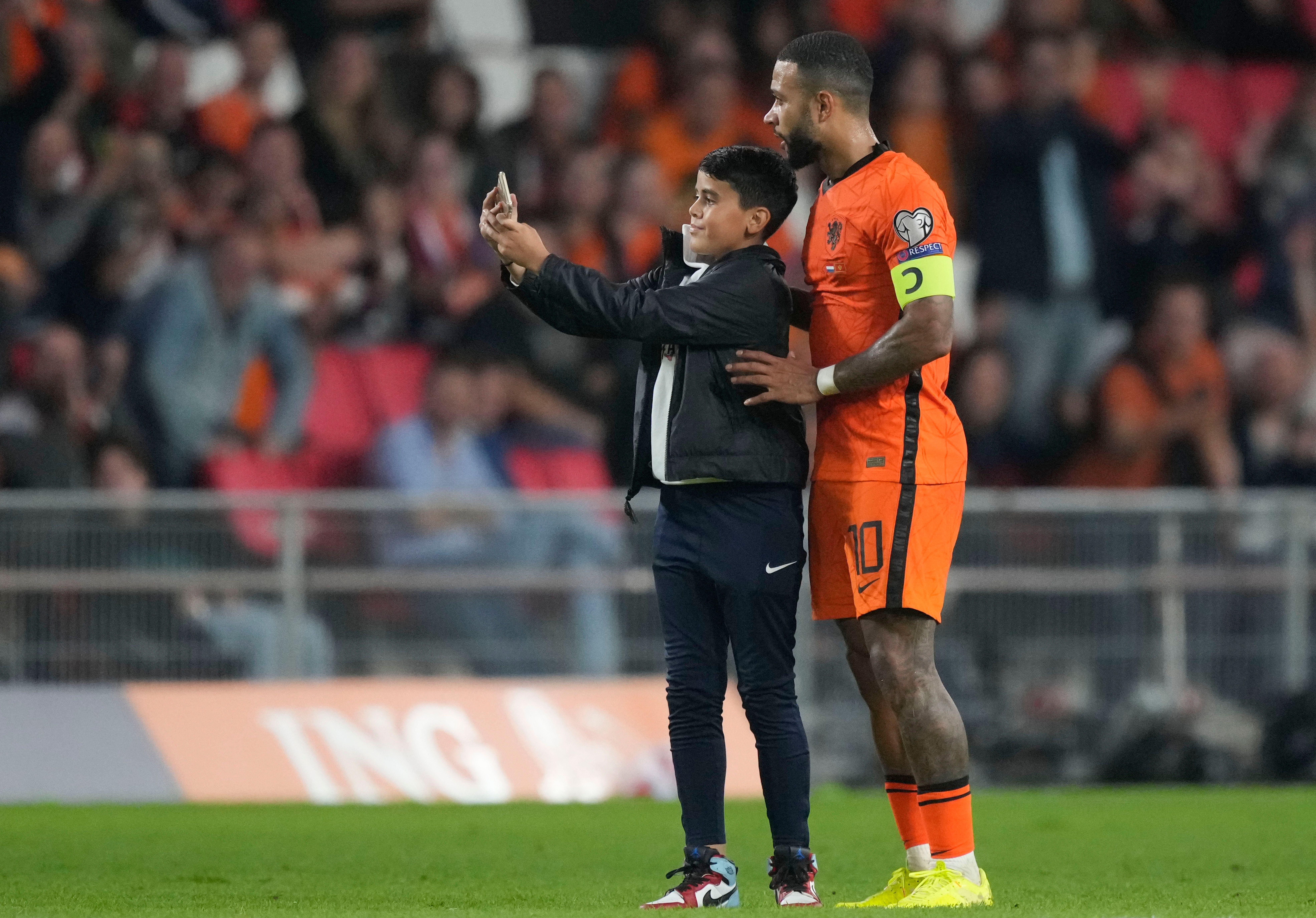 Un jeune fan prend un selfie sur le terrain avec Memphis Depay lors de Pays-Bas-Monténégro,...