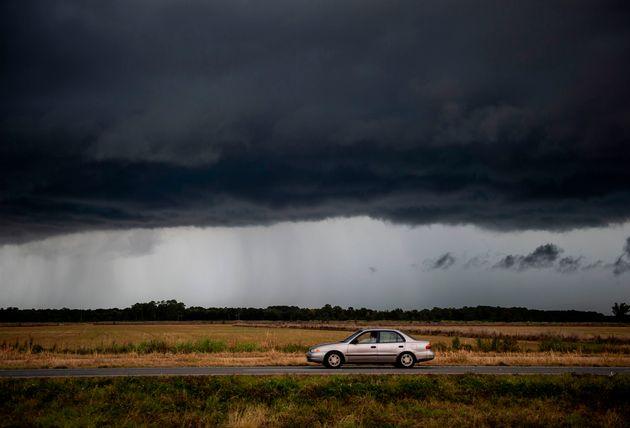 Une voiture roule sous un nuage de pluie menaçant de la tempête tropicale Marco près...
